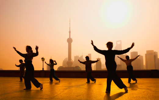 People's Republic of China, Shanghai, The Bund. People practicing tai chi on the Bund. Oriental Pearl Tower and Pudong skyline in background.